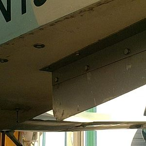 Ventral fin from left side looking forward.  Note bolts out by vertical fuselage.  These run through angle aluminum inside the aircraft to provide lat